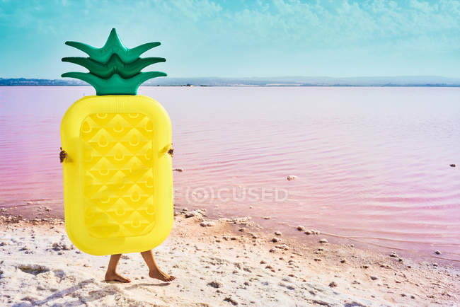 Woman walking on seashore covered with air mattress in form of pineapple in red lagoon — Stock Photo