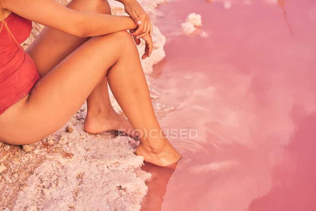 Обрезанный вид стройной женщины, отдыхающей на соленом пляже с розовой водой — стоковое фото