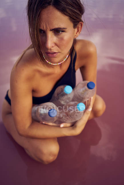 Serious woman in swimwear in water contaminated with plastic bottles at red lagoon — Stock Photo