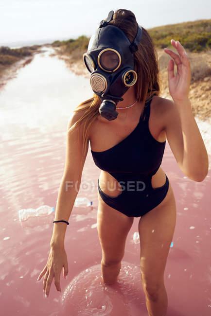 Mujer en traje de baño y máscara respiratoria caminando en agua rosa contaminada con botellas de plástico en la laguna roja - foto de stock