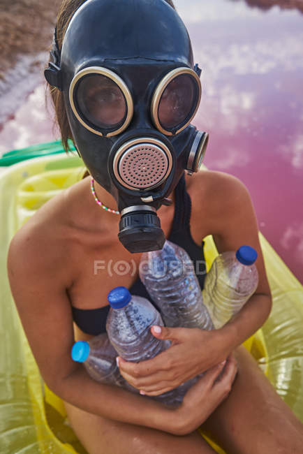 Weibchen in Gasmaske und mit Plastikflaschen im Seewasser — Stockfoto