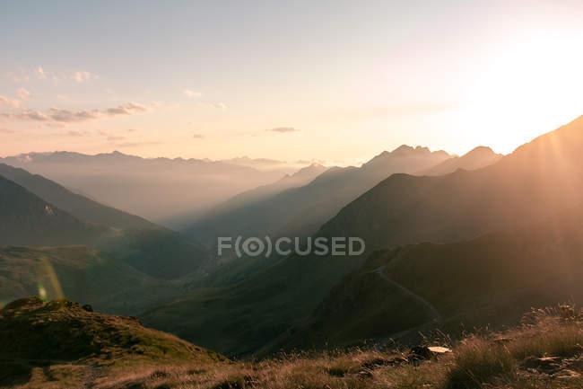 Paisagem nebulosa de montanhas incríveis na luz do sol e caminho entre no dia brilhante — Fotografia de Stock