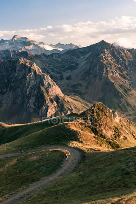 Sentiero sterrato ondato che si estende nell'entroterra fino alle montagne rocciose sotto il cielo nuvoloso alla luce del sole — Foto stock