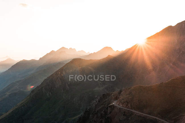 Landscape of amazing mountains in sun light and path between in bright day — Stock Photo