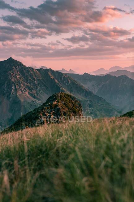 Теплый пейзаж с одиноким камнем в холмистой местности, рядом скалистые горы под красно-серым облачным небом при закатном свете — стоковое фото