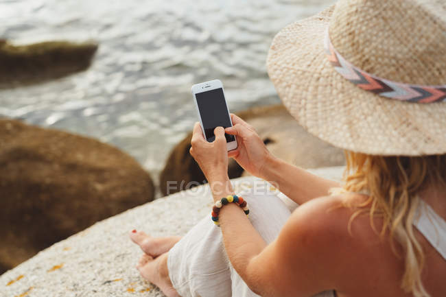 Woman in straw hat sitting on coastal stone and holding smartphone with blank screen — Stock Photo