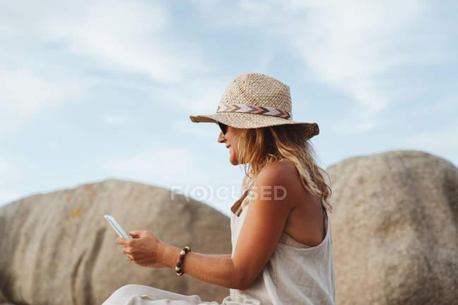 Woman in straw hat sitting on coastal stone and holding smartphone while enjoying holidays — Stock Photo