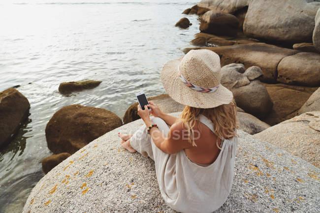 Жінка в солом'яному капелюсі сидить на прибережному камені і тримає смартфон під час відпустки. — стокове фото