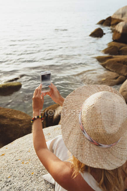 Woman in straw hat sitting on coastal stone and holding smartphone to take a picture while enjoying holidays — Stock Photo