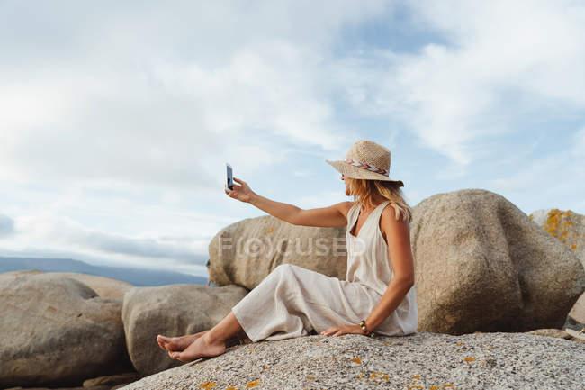Mulher em chapéu de palha sentado em pedra costeira e segurando smartphone para tirar uma foto enquanto desfruta de férias — Fotografia de Stock