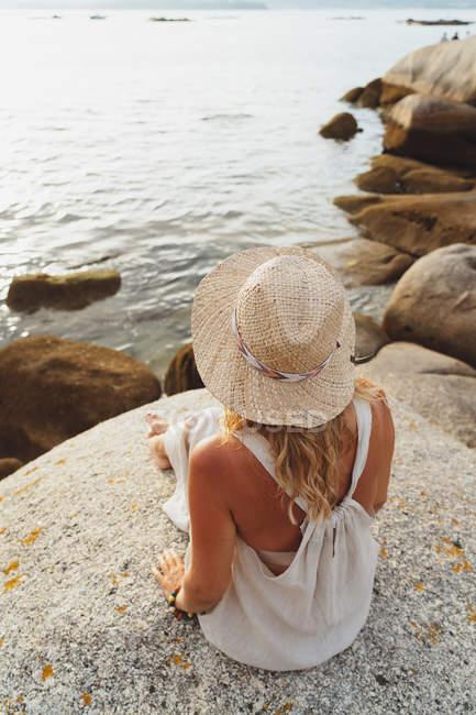 Visão traseira da mulher em chapéu de palha sentado na frente de falésias litorâneas em luz do pôr do sol — Fotografia de Stock