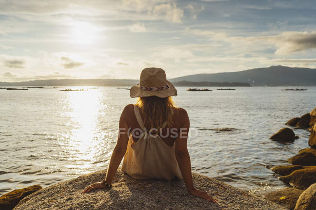 Vista posterior de la mujer rubia en sombrero sentado en piedra en la orilla y disfrutando del paisaje marino en el día nublado - foto de stock