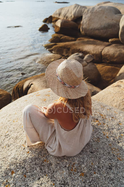 Back view of woman in straw hat sitting in front of seashore cliffs in sunset light — Stock Photo