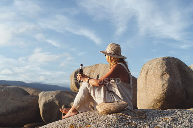 Side view chilling woman sitting on stone at coast and drinking beer from bottle while enjoying seascape in sunlight — Stock Photo