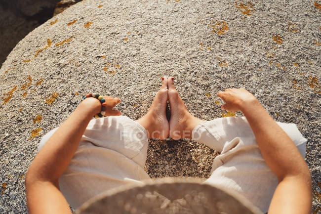 Imagem cortada de mulher sentada em pedra quente áspera e meditando em luz solar calma — Fotografia de Stock
