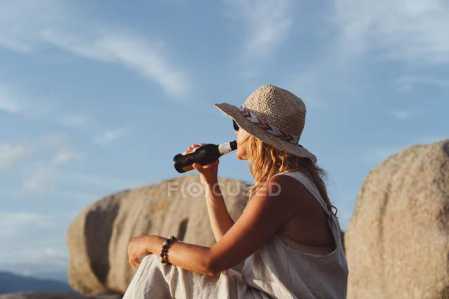 Vista laterale donna agghiacciante seduta sulla pietra sulla costa e bere birra dalla bottiglia mentre si gode pittoresco paesaggio marino alla luce del sole — Foto stock
