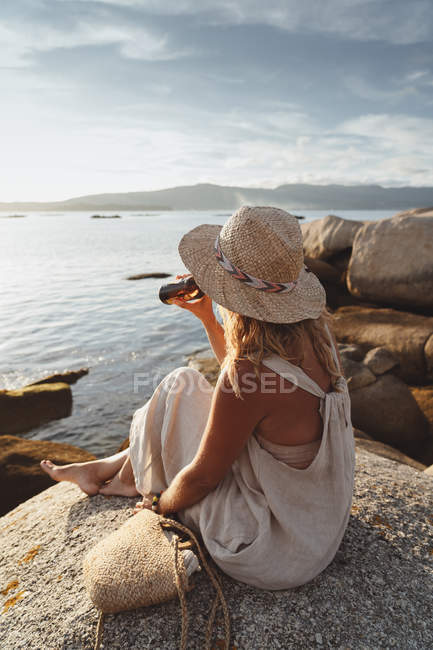 Side view chilling woman sitting on stone at coast and drinking beer from bottle while enjoying picturesque seascape in sunlight — Stock Photo