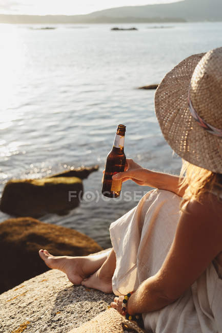Cropped image of woman sitting on stone at coast and drinking beer from bottle while enjoying picturesque seascape in sunlight — Stock Photo