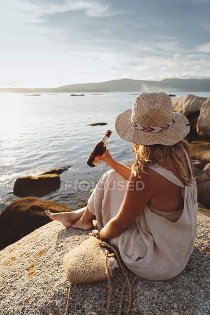Vista lateral mulher gelada sentada em pedra na costa e bebendo cerveja de garrafa enquanto desfruta da pitoresca paisagem marinha à luz do sol — Fotografia de Stock
