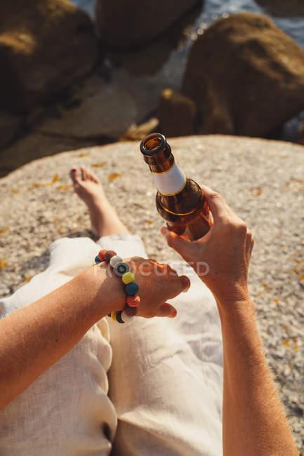 Imagem cortada de mulher sentada em pedra na costa e bebendo cerveja de garrafa enquanto desfruta pitoresca paisagem marinha à luz do sol — Fotografia de Stock