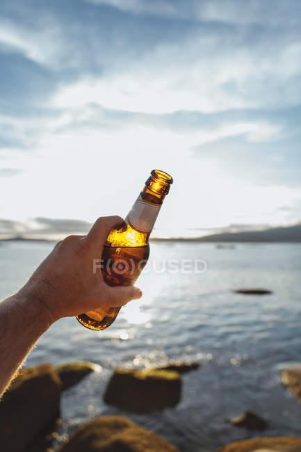 Imagem cortada do homem segurando garrafa brilhante de cerveja contra a luz solar e do mar — Fotografia de Stock