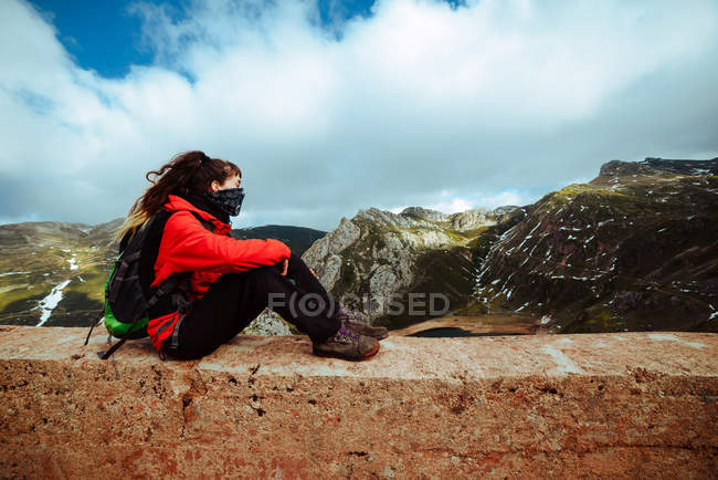 Woman in red jacket and scarf sitting near countryside road on mountain slope on cloudy daytime in amazing nature — Stock Photo
