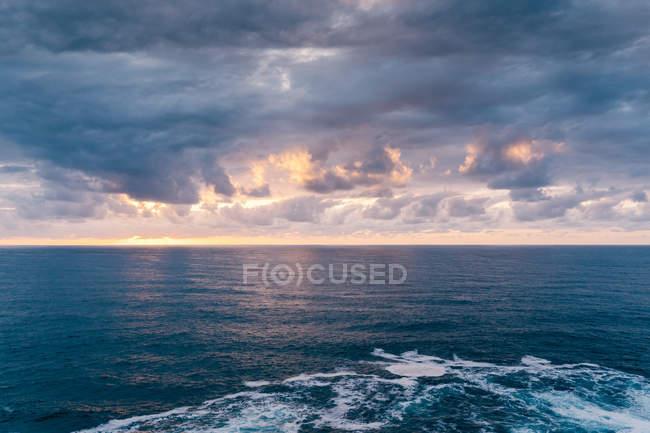 Ciel ensoleillé au-dessus d'une mer tumultueuse avec vagues moussantes en soirée dans la nature — Photo de stock