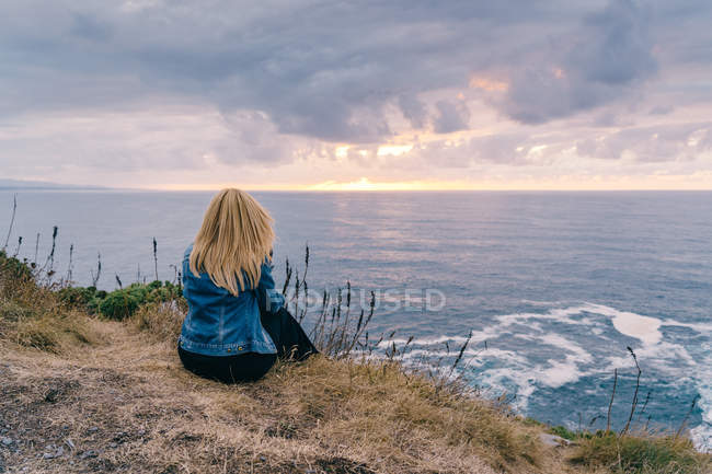 Back view of blond woman chilling and contemplating scenic seascape while sitting alone on calm seashore in clouds — Stock Photo