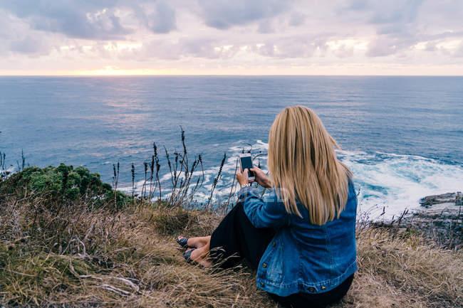 Vista trasera de la señora rubia viajera sentada en el alto acantilado de la costa y tomando una foto de majestuoso atardecer pintoresco paisaje marino - foto de stock