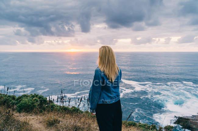 Rückansicht einer blonden Frau, die in Wolken allein am ruhigen Meeresufer chillt und die malerische Landschaft betrachtet — Stockfoto