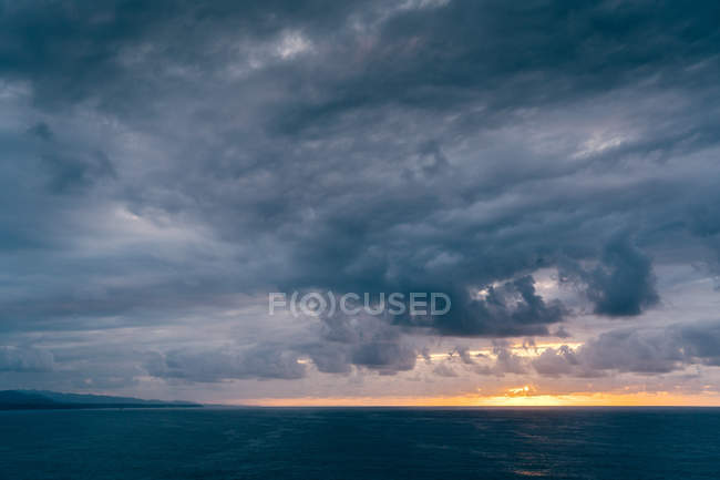 Nuvole grigio scuro vorticoso sul cielo tempestoso tramonto sul mare increspato in serata in natura — Foto stock