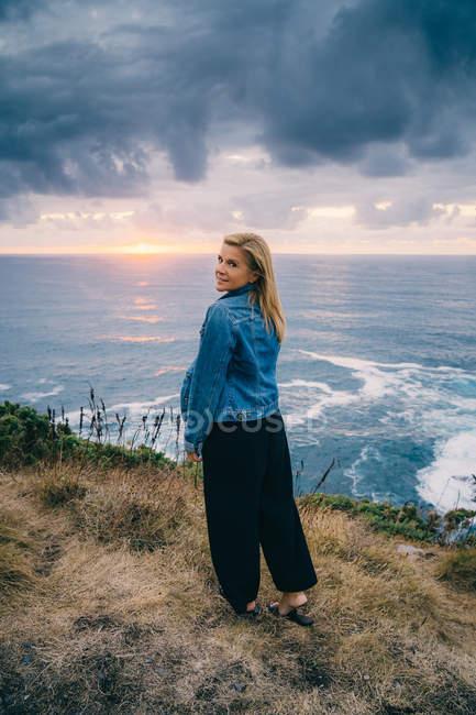 Зворотний погляд на біляву жінку, яка холоне і споглядає мальовниче море, стоячи на спокійному узбережжі в хмарах. — стокове фото