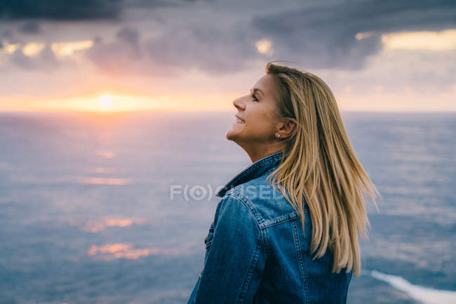 Woman chilling and contemplating scenic seascape while standing alone on calm seashore in clouds — Stock Photo