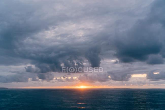 Costa com grama seca perto do mar tempestuoso na noite nublada durante o pôr do sol bonito — Fotografia de Stock