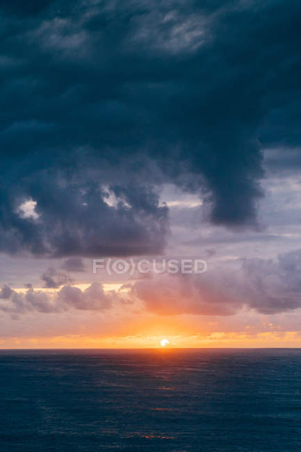 Coast with dry grass near stormy sea in cloudy evening during beautiful sunset — Stock Photo