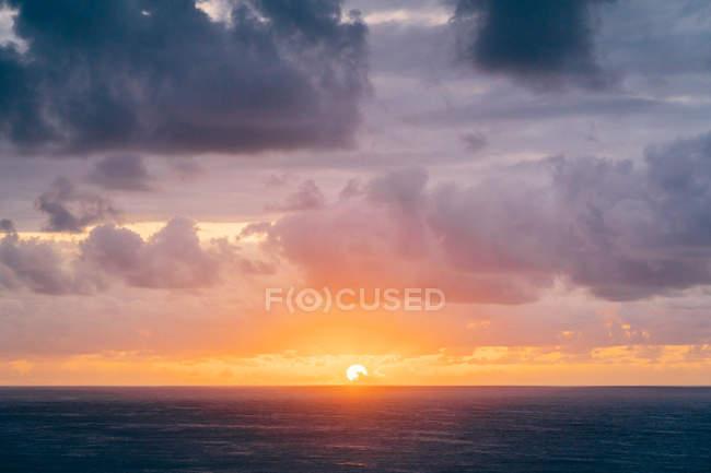 Côte avec herbe sèche près de la mer orageuse dans la soirée nuageuse pendant le beau coucher de soleil — Photo de stock