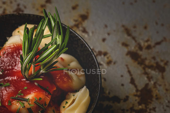 Cooked ravioli with tomato sauce and herbs in bowl next to fork and napkin on table — Stock Photo