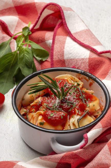 Приготовленные равиоли с томатным соусом и зеленью на сковороде рядом с помидорами на салфетке в столе — стоковое фото