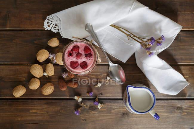 Вид на малиновый коктейль в стеклянной банке с миндальным молоком, подаваемый на деревенском столе с салфеткой — стоковое фото