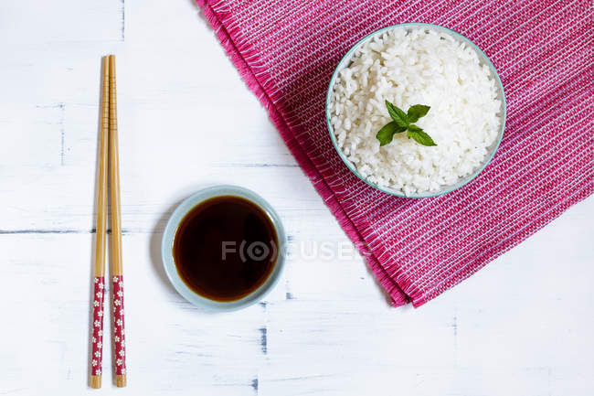 Top view of bowl of traditional Japanese rice on pink towel and chopsticks by saucer with soy sauce on white table. — Stock Photo
