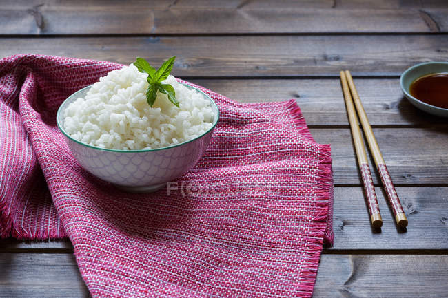 Bowl of traditional Japanese rice on pink towel and chopsticks on wooden table. — Stock Photo