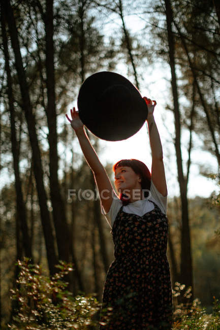 Cheerful woman in retro dress holding a hat walking alone in the forest while looking away — Stock Photo