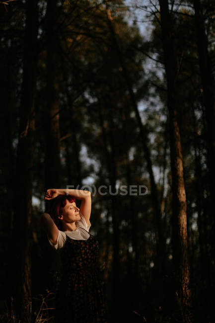 Thoughtful woman enjoying the moment with closed eyes alone in the forest — Stock Photo