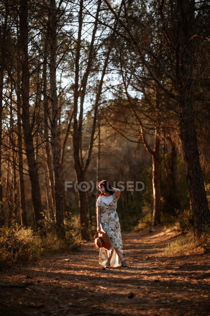 Woman in retro dress and hat walking alone in the forest while looking away — Stock Photo