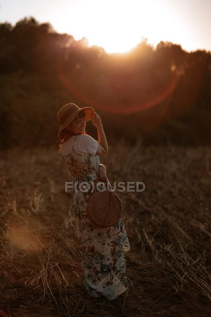 Back view of woman in retro dress and hat walking in field towards sunset sky while looking away — Stock Photo