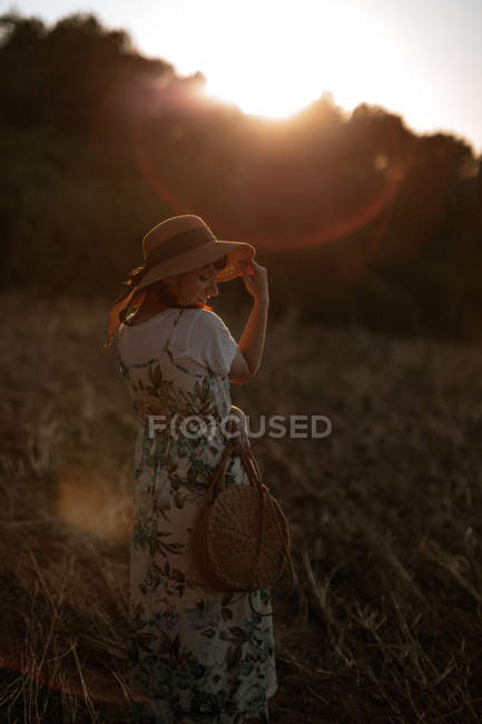 Back view of woman in retro dress and hat walking in field towards sunset sky while looking down — Stock Photo