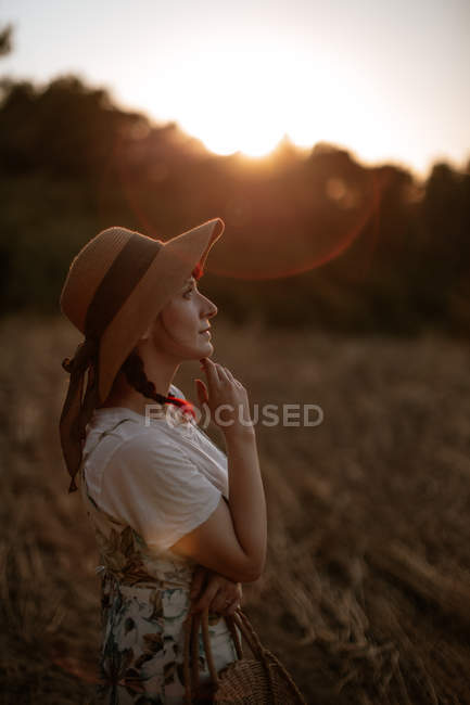 Side view of woman in retro dress and hat walking in field towards sunset sky while looking away — Stock Photo