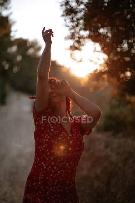 Веселая женщина в красном платье улыбается среди высоких деревьев в солнечный день в зеленом лесу с закрытыми глазами — стоковое фото