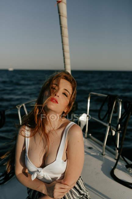 Приваблива і приваблива руда жінка дивиться на камеру під час подорожі на кораблі. — стокове фото