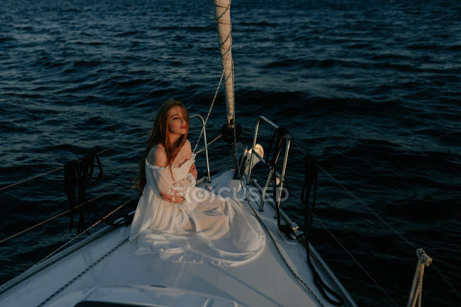 Relaxed beautiful woman  sitting on bow of ship and resting while enjoying sea trip looking away — Stock Photo